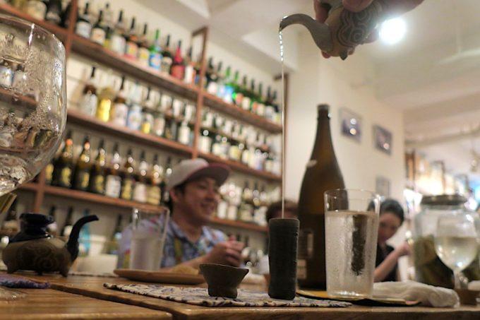 那覇・久米「泡盛倉庫」カラカラで高いところから細く泡盛を注ぐ。