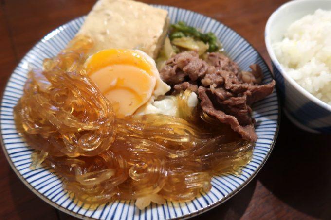 那覇・松山「三笠食堂」スキヤキお皿に乗り切らず、もう1皿分がパックに残った(2020年3月時点)