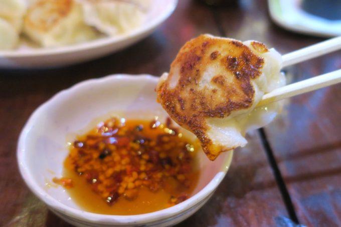 那覇・浮島通り「餃子の店 華」焼き餃子をタレに浸す瞬間。