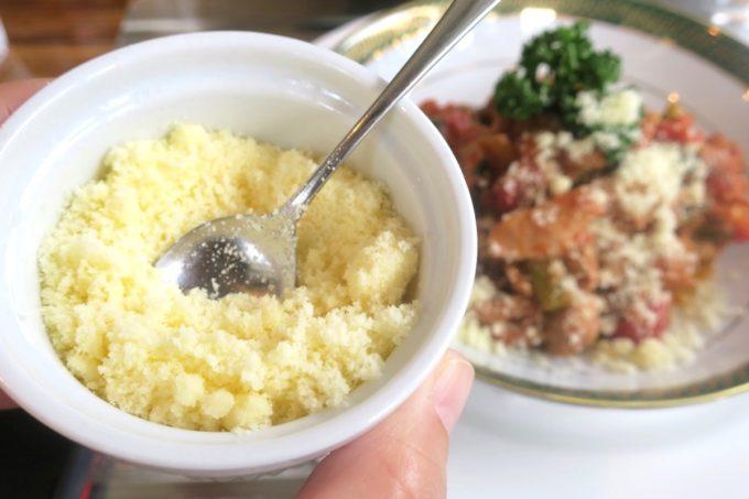 那覇・久米「KYOKAWA 〜Sweets, Food, Drink〜(キョウカワ)」ランチの肉料理にたっぷりパルメザンチーズをふりかける。
