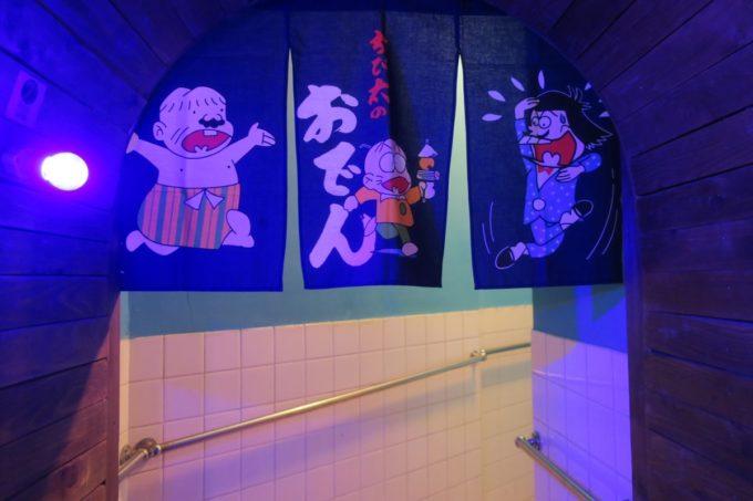 那覇・牧志「酒場TQ(ターコイズ)」トイレの入り口にはおそ松くんののれん。