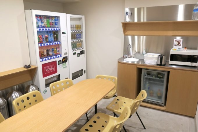 浅草のホステル「マスタードホテル浅草2(MUSTARD HOTEL ASAKUSA2)」のコモンスペース(自販機とテーブル)