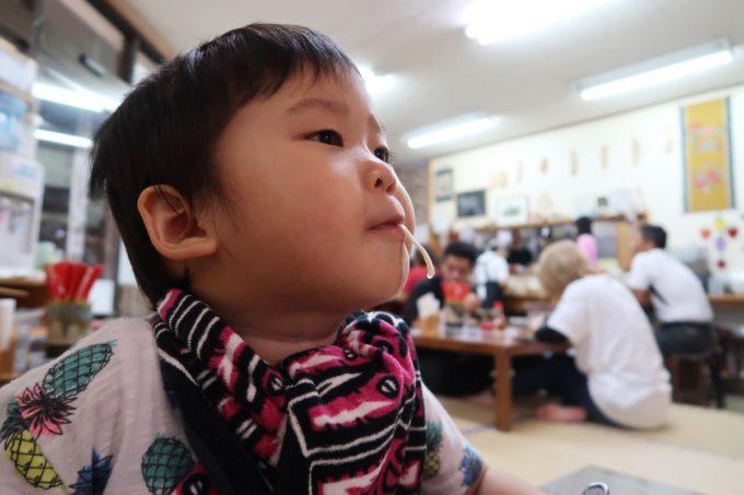 沖縄市泡瀬「米八そば」無料のミニそばをすすって満足げなお子サマー。・