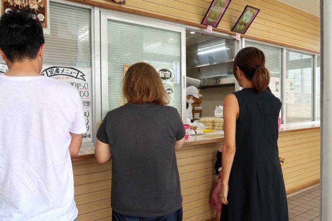 うるま市「丸一食品」の受付に並ぶ人たち。