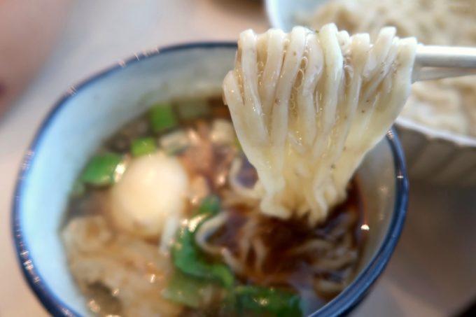 与那原「NAGISA okinawan ramen.(なぎさ おきなわ らーめん)」特製つけ麺(昆布水、1090円)の全粒粉麺をつけダレにどぼん。