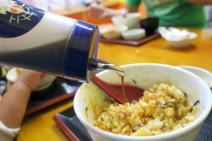 八重瀬・アグリハウスこちんだ内「たまごめし」かつおしょうゆで味を整える。