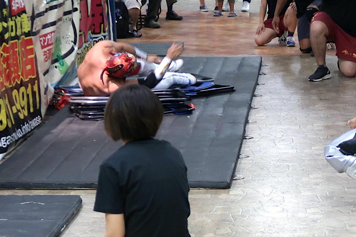 琉球ドラゴンプロレスのハウスショー「我栄トーナメント2020 Aブロック一回戦」エプロン下のパイプ椅子に投げられるグルクンマスク(2020年1月11日)