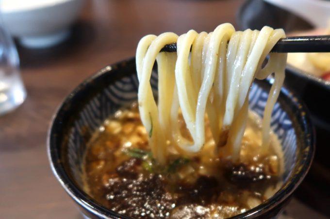 宜野湾「麺処 わた琉」チャーシューつけ麺(1100円)の麺をつけダレにどぼん!