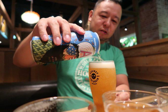 石垣島「Against the Grain(アゲインスト ザ グレイン)」でA BEERという缶ビール(1000円)を注ぐご主人サマー