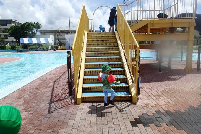 嘉手納町「兼久海浜公園ウォーターガーデン」滑り台(ウォータースライダー)の階段を登るお子サマー