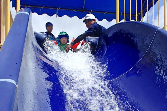 嘉手納町「兼久海浜公園ウォーターガーデン」傾斜が緩い滑り台(ウォータースライダー)に挑むも表情が硬いお子サマー