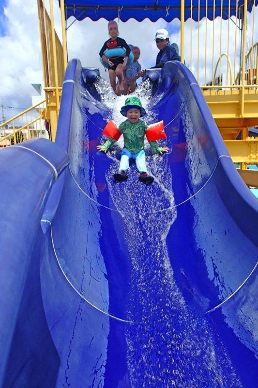 嘉手納町「兼久海浜公園ウォーターガーデン」傾斜が緩い滑り台(ウォータースライダー)を滑るお子サマー