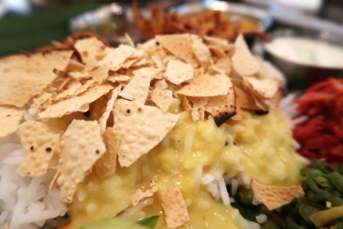那覇・松尾「南インド料理 マリアラム(Malayalam)」お豆のパリパリ塩煎餅(パパド)を割ってご飯の上に。