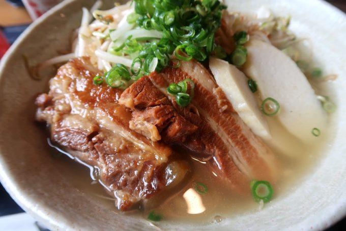 那覇市安謝「おもろ殿内」よくばりおもろそば ジューシーセット(980円)には三枚肉・軟骨ソーキ・野菜が乗せられている