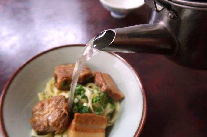 名護市城「八重食堂」セルフでそばのスープを注ぐ