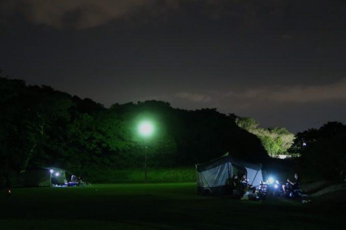 ユインチホテル南城のキャンプ場、夜に灯る各サイトのテント