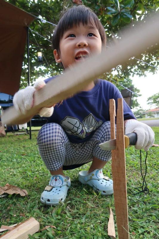 沖縄県東村「つつじエコパーク」のキャンプ場で薪を割るお子サマー