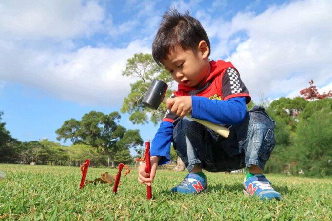 沖縄県総合運動公園キャンプ場でペグを差し始めるお子サマー