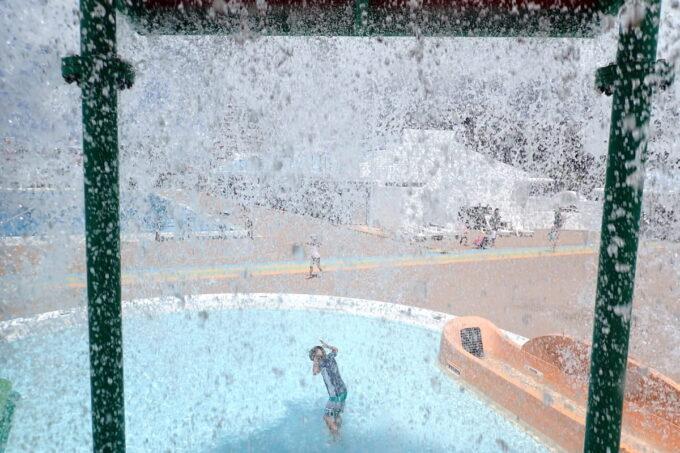 「北谷公園水泳プール」大きなバケツの水がひっくり返る様子を遊具の内側から撮影