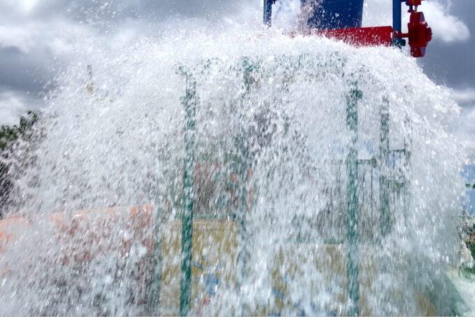 「北谷公園水泳プール」水飛沫を上げ大きなバケツのひっくり返る様子を遊具の外側から撮影