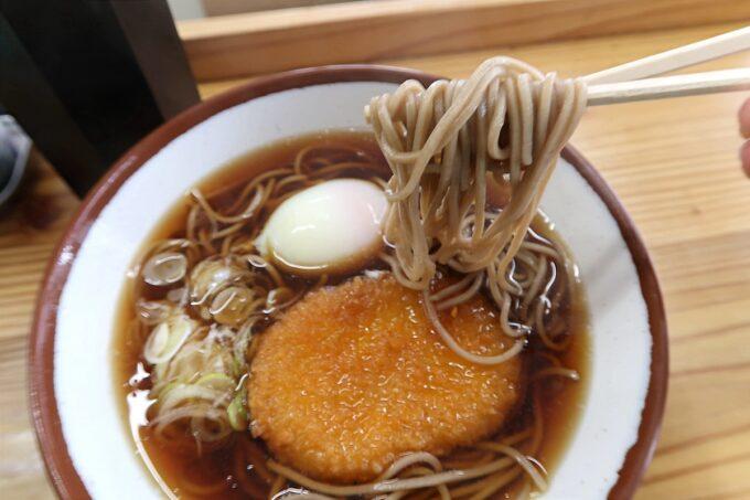 那覇市久茂地「永當蕎麦」コロッケ蕎麦(290円)の蕎麦を箸上げ