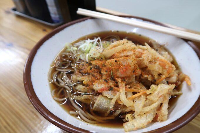 那覇市久茂地「永當蕎麦」かき揚げ蕎麦(390円)に七味をたっぷりかけていただく