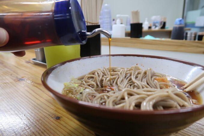 那覇市久茂地「永當蕎麦」かき揚げ蕎麦(390円)に辣油を垂らしていただく