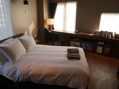 那覇市泊「ホテルプチスイート崇元寺石門」4階LIBRARYの客室(ベッドサイド)
