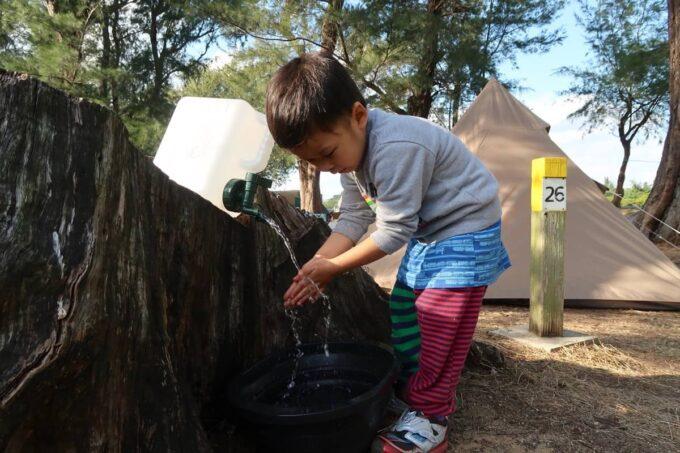 沖縄県金武町「ネイチャーみらい館」の切り株にタンクを置いて手を洗う
