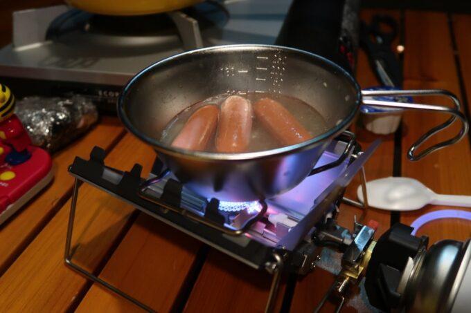 沖縄県金武町「ネイチャーみらい館」購入したてのシェラカップでソーセージを茹でる