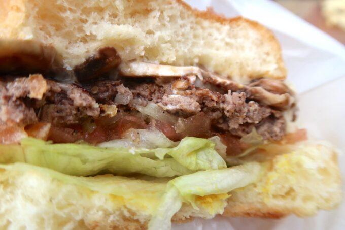 北谷町美浜「Chatan Burger Base Atabii's(チャタンハンバーガーベース アタビーズ)」アタビーズサルサマッシュルームモッツァレラバーガー(1430円)をかぶりつく