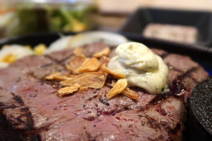 豊見城「OK STEAK(オーケーステーキ)」赤身ステーキ300g(1100円)の上にはガーリックチップとガーリックバターが載せられている