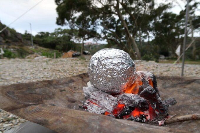 沖縄・本部町「KARST CAMP SITE(カルストキャンプサイト)」焚火にアルミ箔で巻いた玉ねぎを放り込む