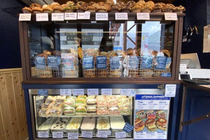 愛媛県松山市「ネイビーベーグルズ(NAVY BAGELS)」の店内ショーケースに並ぶベーグルとカップケーキ