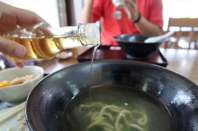 中城村「麺家にらい」あっさりクリアなスープにコーレーグスを垂らす