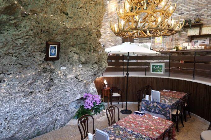 南城市「ガーデンレストラン花さんご」店内にある琉球石灰岩の大きな岩とテーブル席