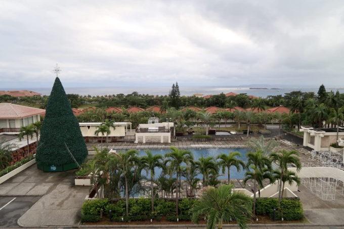 沖縄の老舗「カヌチャリゾート」ノースウィングのジュニアスイートからガーデンプールを眺める